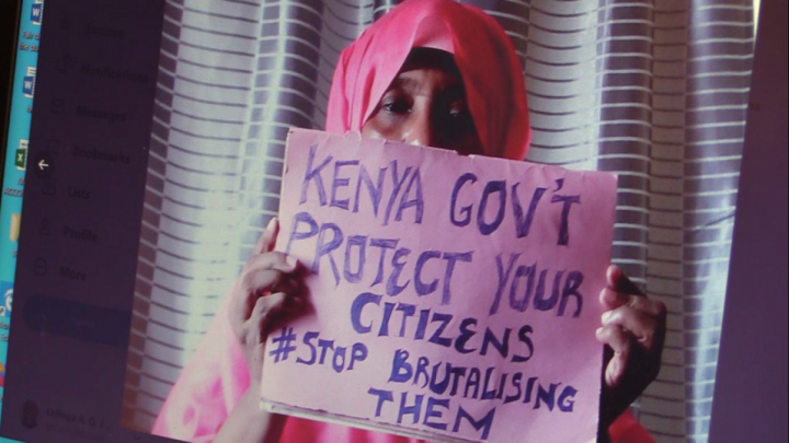 "Woman holding a poster saying ""Kenya government protect your citizens #Stop brutalising them"""