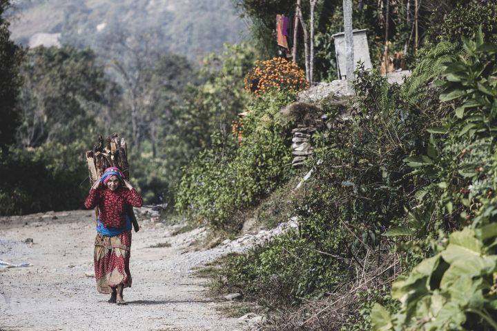 Nainen kantaa polttopuita tiellä